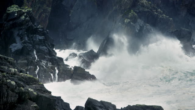 MS SLO MO agitated waves breaking on rocky shore with stormy weather and wind / Lewis Island, Scotland, United Kingdom