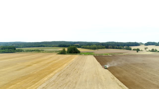 Agricultural tractor sowing and cultivating agricultural field.