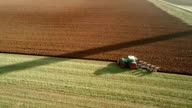 AERIAL: Agriculture - Tractor plowing a field