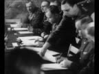 Aide removes copy of German instrument of surrender after German Gen Alfred Jodl has signed it he prepares to sign another / US Gen Walter Bedell...