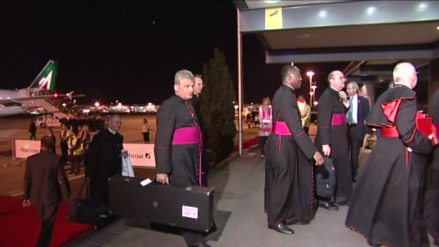 Aides accompanying Pope Benedict XVl follow him into Heathrow VIP suite as they arrive for visit to Britain One carries large case possibly...