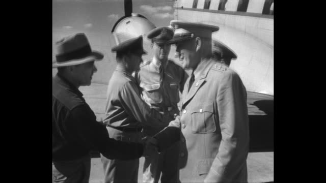 US Air Force officer getting off plane at airfield and being greeted by other officers / he is greeted by other officers and official / two shots of...