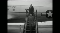 US Air Force plane taxis past camera / Dulles comes down steps from airplane / he is greeted by officials / CU Dulles talking with two officials /...