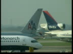 Air passengers delayed after computer crash ITN Airplane tail fins as planes taxi PAN to plane taking off PAN
