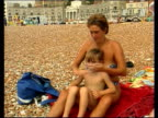 Smog warning Sussex Hastings Mother on beach applying sun cream to her son