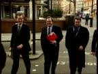 MPs Rebel ITN ENGLAND London John Prescott MP towards past across road into building with advisers INT BV Prescott away through foyer TRACK MS...