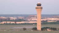 Air traffic control tower with commuter jet (Embrear ERJ) crossing frame on take off//DFW International Airport, Dallas-Fort Worth, Texas, USA