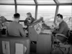 Air traffic controllers work in the control tower at London Airport