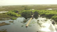 MS AERIAL DS Airboat driving towards three huts near water in everglades / Florida, United States