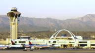 WS Aircraft landing at LAX airport behind control tower / Los Angeles, California, USA