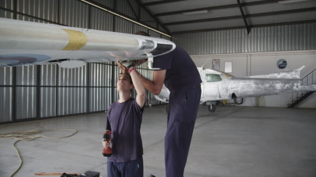 aircraft mechanics working on airplane wing in hangar, RED R3D 4K