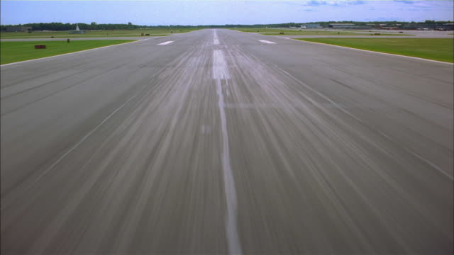 Aircraft point of view landing on and taking off runway towards traffic on highway / Albany Airport, New York