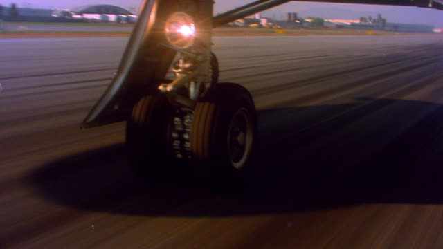 Aircraft point of view of airplane wheel on runway during take off from Bob Hope Airport to aerial from outside plane / Burbank, California