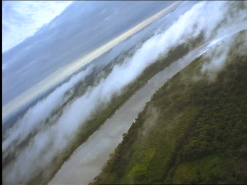 AERIAL aircraft point of view over cloud-covered Amazonian jungle + Manu River / Peru