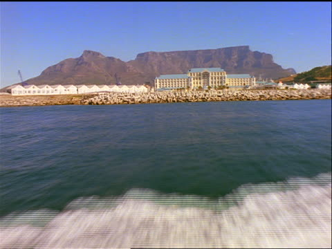 AERIAL aircraft point of view over water + speedboat towards Cape Town / Table Mountain in background / South Africa