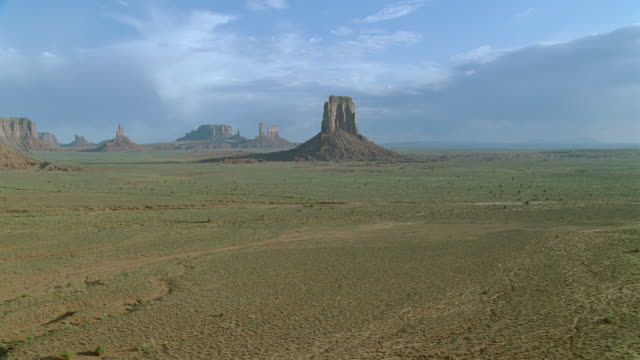 Aircraft point of view past butte, over desert shrubs / Monument Valley