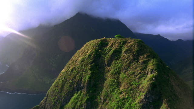 AERIAL aircraft point of view toward summit of hill in ocean with man flying kite / mountains in background / Hawaii
