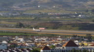 TS aircraft taking off from Malaga (IATA: AGP / ICAO: LEMG) airport; camera stops on new terminal T3 on right, old terminal T2 on left / Malaga, Andalusia, Spain
