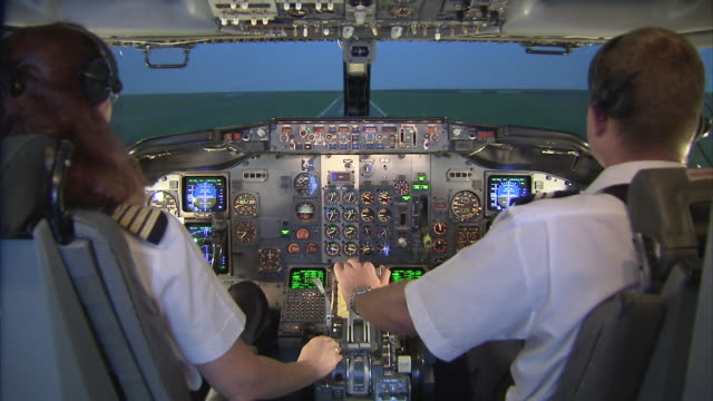 Aircrew training in Boeing 737 400 simulator, female captain and male FO performing landing / Johannesburg, Gauteng, South Africa