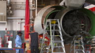 Airline mechanics go to work on jet engine in hanger/DFW International Airport, Dallas-Fort Worth, Texas, USA