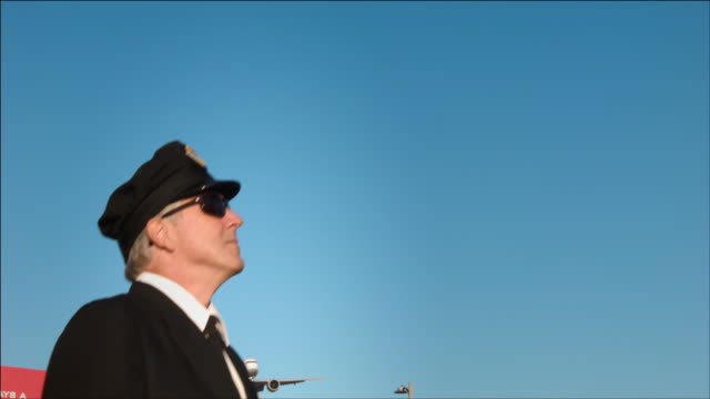 M/S airline pilot steps into frame, airplane passes overhead: ANA Boeing-777