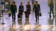 WS Airline pilots and flight attendants walking through airport lounge with luggage, talking / Los Angeles, California, USA
