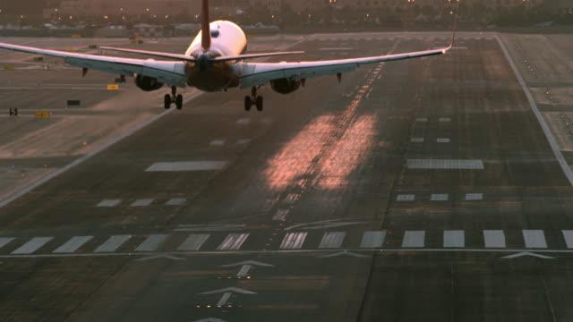 HA WS airliner passenger jet landing on airport runway at dusk creating a wavy pattern of air turbulence around aircraft / San Diego, California, USA