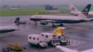T/L, WS, HA, Airplane and trucks parked on runway, England