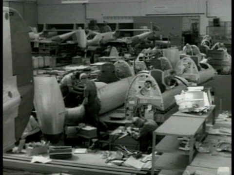Airplane factory INT HA WS Swedish workers building fighter airplanes VS Working on wing tail wing EXT MS Men pushing completed jet propelled...