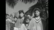 Airplane flying low overland passing behind palm trees / Seminole women and children / men in elaborate striped jackets / mothers and children