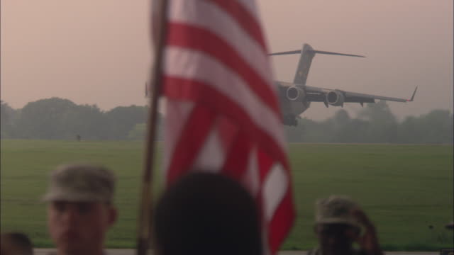 TS Airplane landing on runway as soldiers and families look on / North Charleston, South Carolina, United States