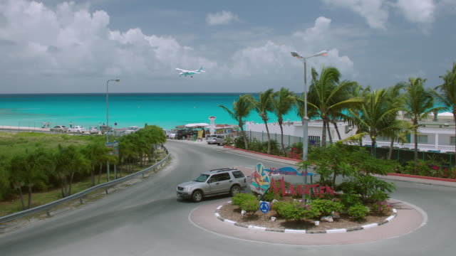 WS Airplane landing over Maho Beach, car in traffic circle in foreground / St. Maarten