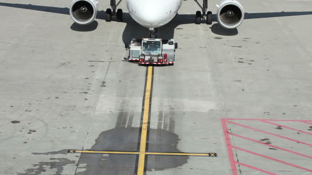 Airplane on tarmac of an airport is getting serviced