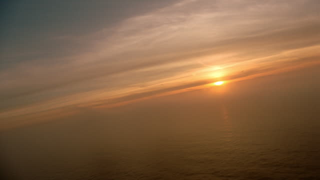 AERIAL airplane point of view over ocean towards horizon at sunset