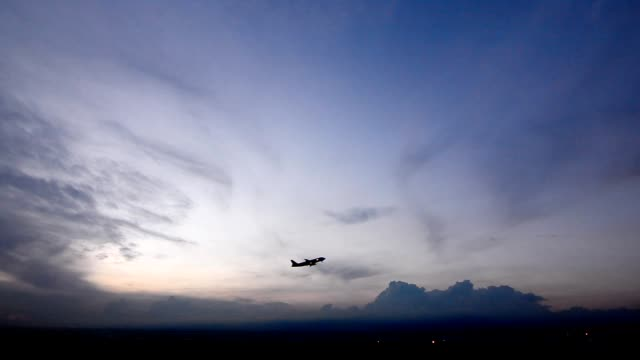 Airplane taking off from airport at sunset