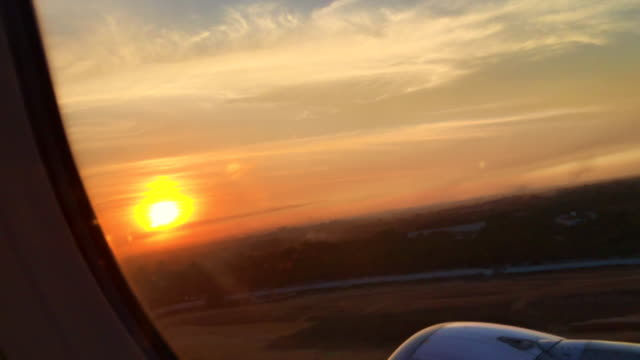 airplane taking off from airport ground to sun setting sky