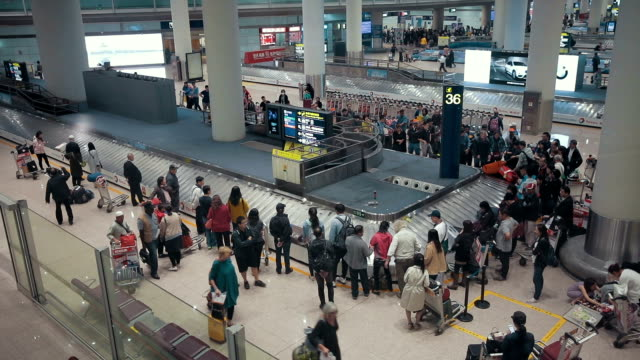 Airplane travelers are waiting for their luggage from a conveyor belt at Beijing International Airport,China