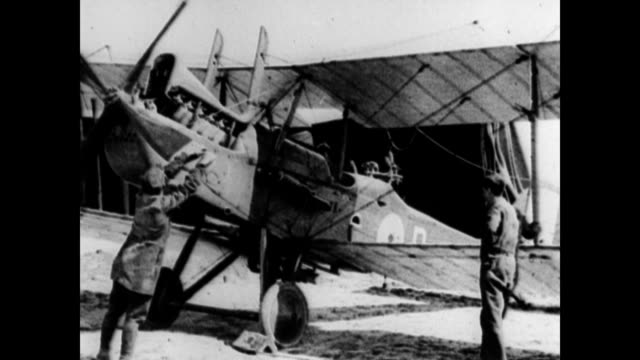 Airplanes on an air field with hangars and soldiers in the background / Leonard S Hobbs perched on the edge of a workspace with several large dials...
