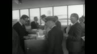 Airplanes parked on the runway / passengers line up inside the terminal / collect tickets and go on board plane / machinists performing checks and...