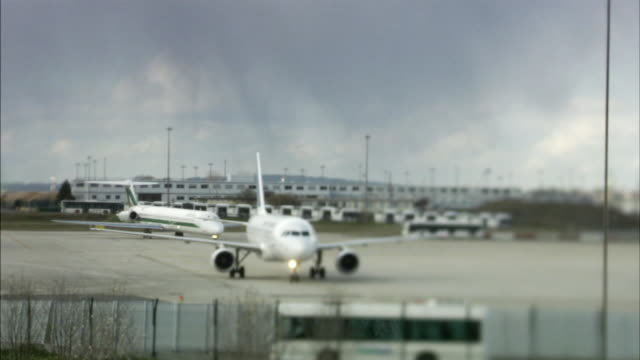 MS SELECTIVE FOCUS Airplanes taxiing on tarmac, silhouettes of passengers in foreground, Paris-Charles De Gaulle Airport, Paris, France