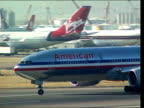 Airport expansion plans announced LIB American Airlines plane taxiing past parked planes GROUND TO AIR Plane over after take off as undercarriage...