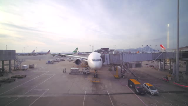 Airport gates, luggage loading, aircraft traffic, utility vehicles and tracks driving around parked airplane
