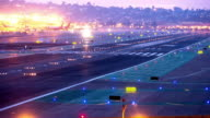 WS HA T/L  airport runway at dusk with blue runway status lights while passenger jets land one after the other and other planes in background taxi towards departure / San Diego, California, USA