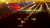 T/L HA LS airport runway at night with  glowing runway lights as jetliners take off and land / San Diego, California, USA