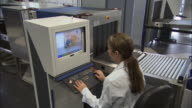 MS Airport security worker looking at x-ray screen as woman goes through checkpoint/ Munich, Germany