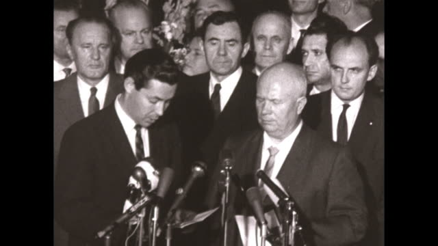 Airport tarmac man with Khrushchev reads a statement before microphones Khrushchev then walks up the stairs to his plane waves to the crowd