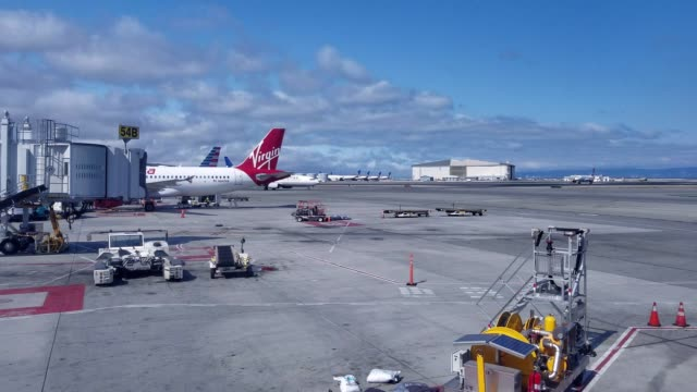 Airport tarmac outside Terminal 2 at San Francisco International Airport on a sunny day with Virgin America jet aircraft visible United Airlines jet...