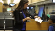 Airport ticket agent checking tickets of passengers