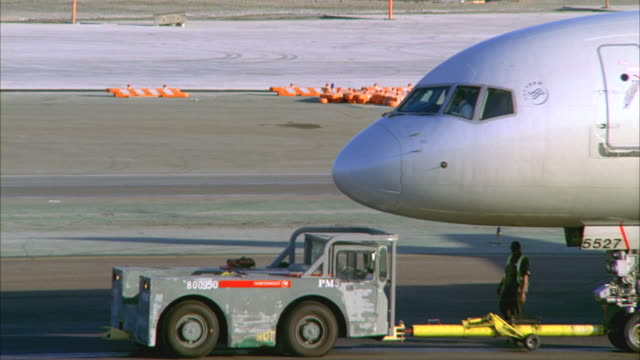CU, Airport vehicle towing commercial aircraft on tarmac, Los Angeles, California, USA