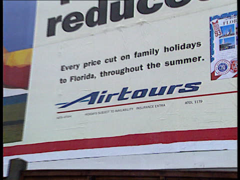 Airtours billboard ZOOM IN Heathrow Airport INT TGV People around checkin desks in airport terminal LA Passengers pushing luggage trolleys along past